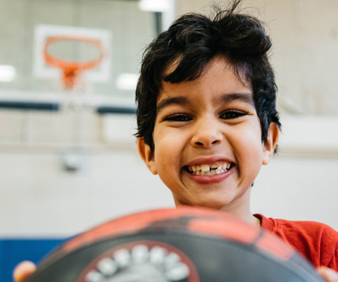 Boy in Rexdale Hub gym with basketball